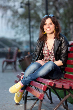 Beautiful girl sitting on a bench in a city park in the evening photo