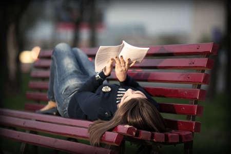 Beautiful girl reading a book on a bench in a city park in the evening