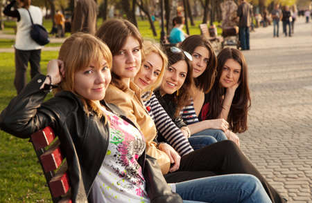 Girls sitting on a bench in city park photo