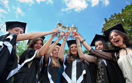 bachelor s degree: Bachelor graduates celebrate with a glass of white wine in mantles