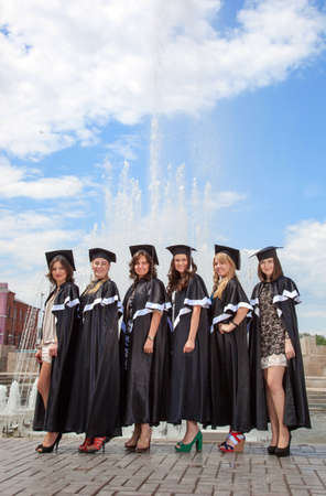 bachelor s degree: Graduates in robes near the fountain in the background of blue sky