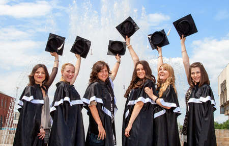 Graduates in robes near the fountain in the background of blue sky photo