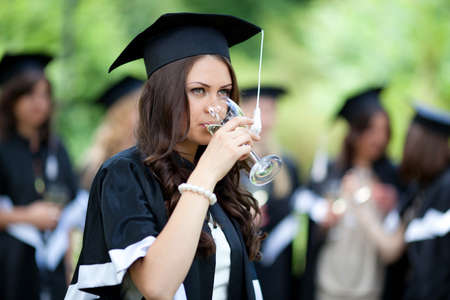 Bachelor graduates celebrate with a glass of white wine in mantles photo