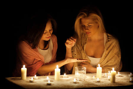 Two girls guessing in the darkness with candles