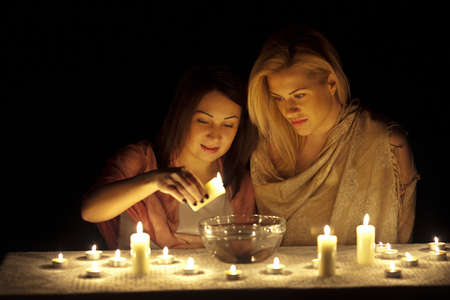 Two girls guessing in the darkness with candles Stock Photo - 14748887