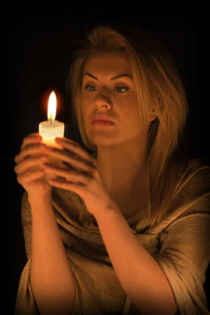 Beautiful girl with a candle in the dark Stock Photo