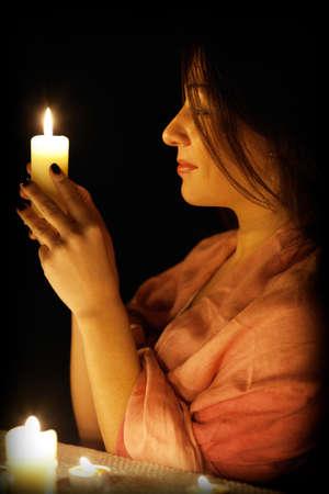 rituales: Hermosa chica con una vela en la oscuridad Foto de archivo