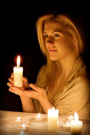 Beautiful girl with a candle in the dark photo
