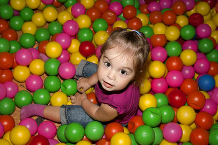 Portrait of a little girl sitting among colorful balls photo
