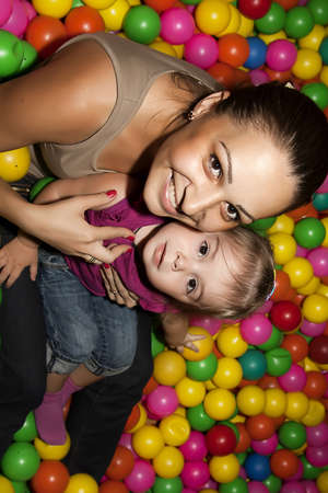 Portrait of a little girl and her mother sitting among colorful balls photo