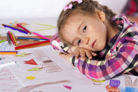 A tired child - an artist with a sketch and colored pencils in a checkered shirt on a white background photo