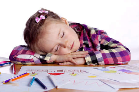 tiredness: Sleeping child - an artist with sketch and colored pencils in a checkered shirt on a white background