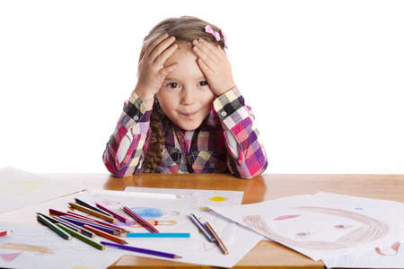 Child - an artist with a sketch and colored pencils in a checkered shirt on a white background photo
