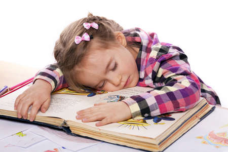 A child sleeps on a book in a plaid shirt on a white background photo