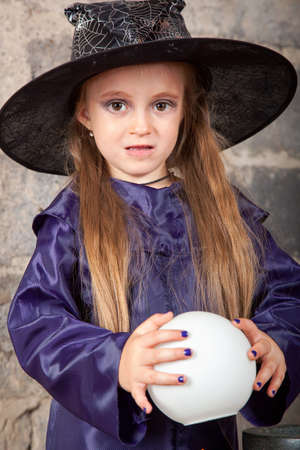 Little witch with magic sphere photo