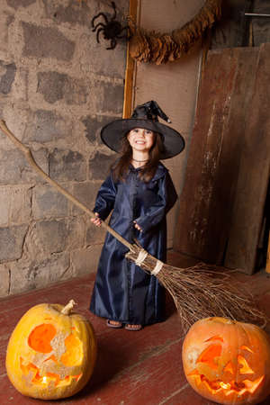 bewitchment: Little witch with a broom in an old abandoned house with Halloween pumpkins Stock Photo