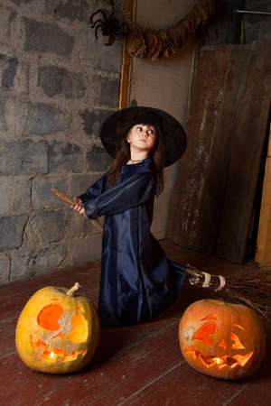 witchery: Little witch with a broom in an old abandoned house with Halloween pumpkins Stock Photo