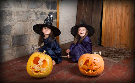 bewitchment: Two little witch in an abandoned house sitting on a broom with Halloween pumpkins