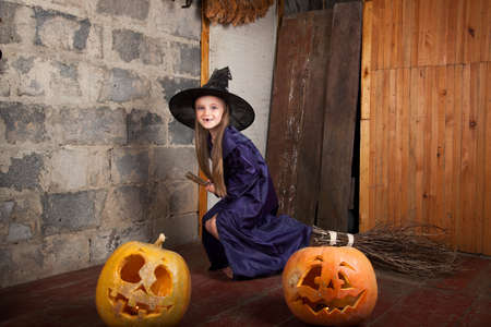 Little witch with a broom in an old abandoned house with Halloween pumpkins photo