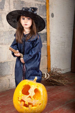 Little witch with a broom in an old abandoned house with Halloween pumpkins Stock Photo