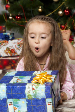 Girl in pajamas lying under the Christmas tree with gift in hand photo