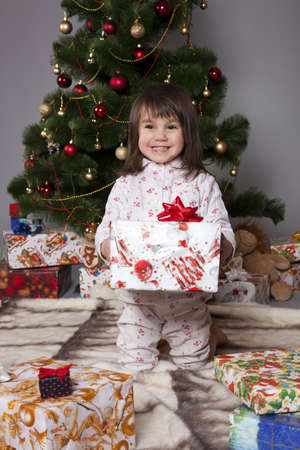 Girl in pajamas sitting under the Christmas tree with gift in hand photo