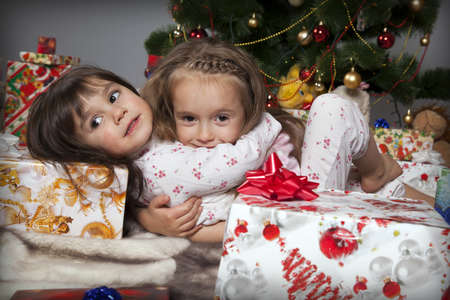 Two girls in pajamas sitting under the Christmas tree with gifts photo