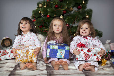 Three girls in pajamas sitting under the Christmas tree with gifts in their hands photo