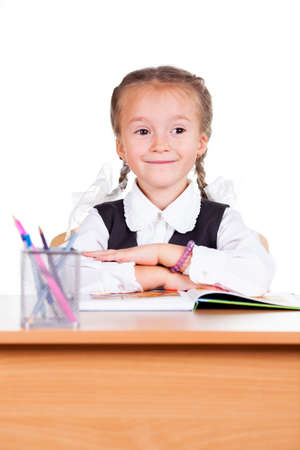 exemplary: Portrait of schoolgirl with books sitting at a desk in the classroom