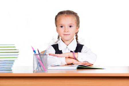 Portrait of schoolgirl with books sitting at a desk in the classroom