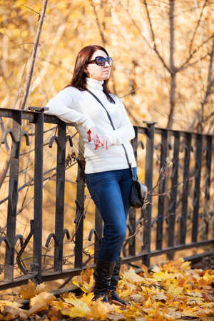 Fashion pretty girl in autumn park looking into the distance
