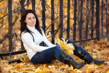 Fashion pretty girl in the autumn park with a bunch of yellow maple leaves