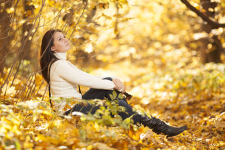Fashion pretty girl in autumn wood looking into the distance Stock Photo