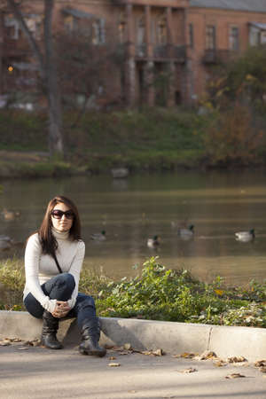 Fashion girl in autumn park near the lake with floating ducks in front of the old mansion Stock Photo
