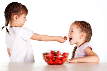 Two little girls feed each other strawberries with a full bowl of strawberries Stock Photo