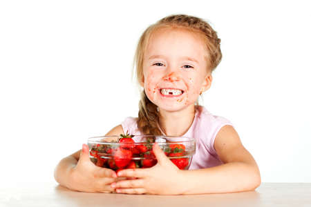 Little girl eating strawberries with a full bowl of strawberries