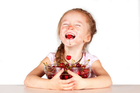 Little girl eating cherry with a full bowl of cherry