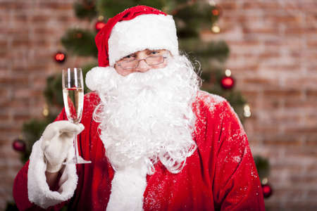 Santa Claus with a glass of sparkling wine champagne near a Christmas tree photo
