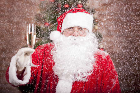 Santa Claus with a glass of sparkling wine champagne under snowfall near a Christmas tree photo