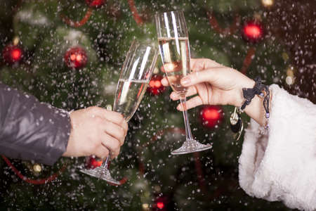 felicitation: Christmas New Years toast on the background of the Christmas tree in snow Stock Photo