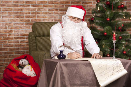 suddenness: Santa Claus writes a list on the background of the Christmas tree