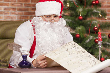 felicitation: Santa Claus checks his list on the background of the Christmas tree