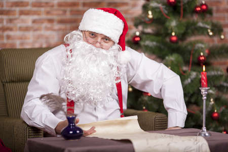 felicitation: Santa Claus writes a list on the background of the Christmas tree