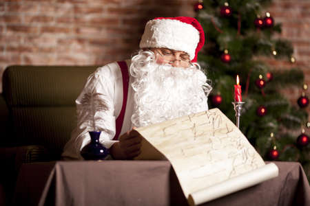 suddenness: Santa Claus checks his list on the background of the Christmas tree