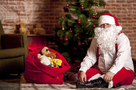 santa s bag: Santa Claus with a bag of gifts on the background of the Christmas tree Stock Photo