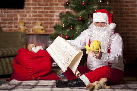 santa s bag: Santa Claus checks his list on the background of the Christmas tree