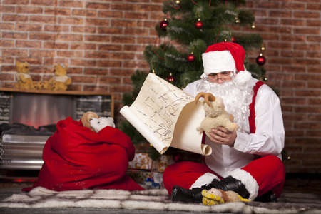 santa s bag: Santa Claus checks his list on the background of the Christmas tree