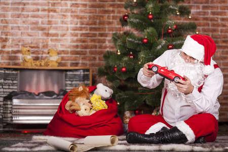 bounty: Papá Noel que juega con los juguetes en el fondo del árbol de navidad y la bolsa con regalos