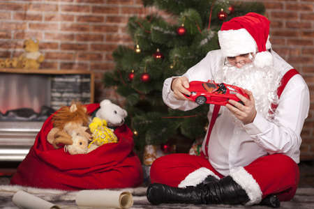 santa s bag: Santa Claus played with toys on the background of the Christmas tree and bag with gifts