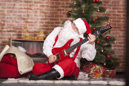 suddenness: Santa Claus plays the guitar on the background of the Christmas tree and bag with gifts Stock Photo